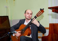 年轻吉他弹奏者坐与一把吉他的阶段在他的手上 免版税图库摄影
