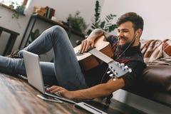 年轻吉他弹奏者行家在家坐拿着吉他耳机音乐浏览膝上型计算机的地板 库存照片
