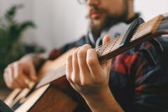 年轻吉他弹奏者行家在家有吉他品柱特写镜头的 免版税库存照片