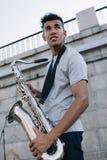 年轻和愉快的非裔美国人的街道音乐家藏品萨克斯管 免版税库存图片