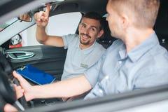 年轻和有胡子的顾问在汽车坐 他看顾客和点  人微笑年轻人 采购员坐前面 免版税图库摄影