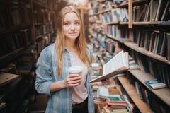 年轻和美丽的学生在图书馆里 她拿着一杯咖啡在右手和一本书的在左边一 女孩是 图库摄影