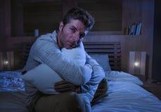年轻哀伤和绝望人醒夜间在看起来被注重的哭泣的单独hol的黑暗遭受的消沉和忧虑的床上 图库摄影