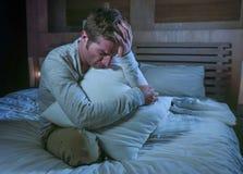 年轻哀伤和绝望人醒夜间在看起来被注重的哭泣的单独hol的黑暗遭受的消沉和忧虑的床上 免版税库存图片