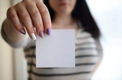 年轻哀伤的女孩显示一个白色贴纸 白种人浅黑肤色的男人藏品 图库摄影