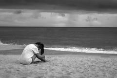 年轻哀伤的妇女坐哭泣在雨中的海滩 E 库存图片