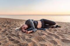 年轻哀伤的被抛弃的妇女在与日落的一个沙滩说谎在背景 免版税库存照片