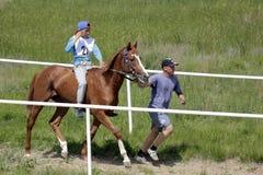 年轻哈萨克人男孩骑一匹纯净的breeded哈萨克人马并且为赛跑与他的教练员做准备 图库摄影