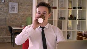 年轻商人与膝上型计算机和饮用的咖啡一起使用在办公室,观看在照相机,企业概念 股票视频