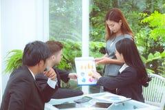 年轻商人做会议和谈话为分析与运作在办公室的图表的行销 免版税库存照片