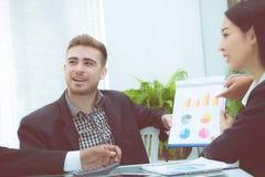 年轻商人做会议和谈话为分析运作在办公室的行销在书桌 免版税库存图片