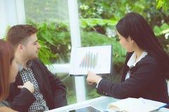 年轻商人做会议和谈话为分析运作在办公室的行销在书桌 免版税库存照片