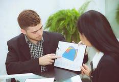 年轻商人做会议和谈话为分析运作在办公室的行销在书桌 免版税图库摄影