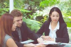 年轻商人做会议和谈话为分析运作在办公室的行销在书桌 图库摄影