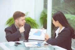 年轻商人做会议和谈话为分析运作在办公室的行销在书桌 库存照片