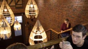 年轻商人喝在时髦咖啡馆的热奶咖啡户内 股票视频