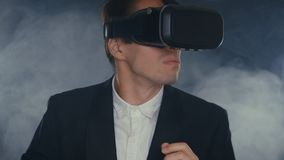年轻商人在一间发烟性黑屋子使用虚拟现实玻璃 影视素材