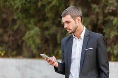 年轻商人在他的手上的看他的电话 免版税库存图片