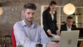 年轻商人在办公室观看膝上型计算机,观看在照相机,微笑,人们是与技术的网络 股票视频