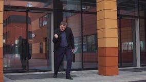 年轻商人在商业中心附近在他的手上的跳舞拿着一个公文包 慢的行动 股票视频