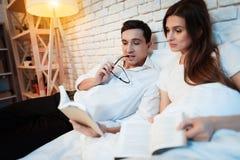 年轻商人在床上读书与他的妻子 他们谈论事务 免版税库存照片