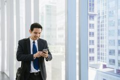 年轻商人在机场 使用智能手机微笑的愉快的里面办公楼的偶然都市专业商人 免版税库存图片