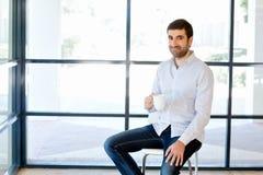 年轻商人坐一把凳子在办公室 免版税图库摄影