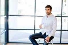 年轻商人坐一把凳子在办公室 图库摄影