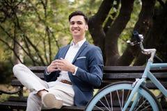 年轻商人坐一条长凳在一个公园,有自行车的 库存图片