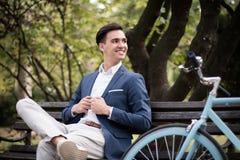 年轻商人坐一条长凳在一个公园,有自行车的 免版税库存图片