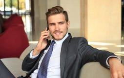年轻商人坐在沙发放松了在打电话的旅馆大厅,等待某人 库存图片