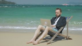 年轻商人完成工作使用膝上型计算机,当坐海滨时 股票录像