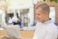 年轻商人寻找在报纸的一个工作 免版税库存照片