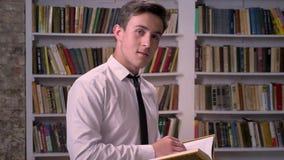 年轻商人是阅读书在图书馆里,观看在照相机,放松概念 股票视频