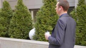 年轻商人步行和主角在无线耳机的企业交谈在他的耳朵 股票录像