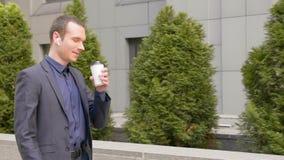 年轻商人步行和主角在无线耳机的企业交谈在他的耳朵 影视素材