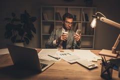 年轻商人用使用智能手机的咖啡在夜间 免版税库存图片