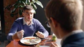 年轻商人谈话与男性同事,当吃早餐在咖啡馆时 股票视频
