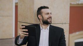 年轻商人谈话在有片剂的计算机上与他的妻子的录影闲谈 使用app的商人有录影 免版税库存图片