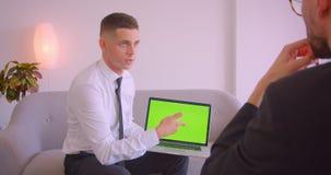 年轻商人陈列膝上型计算机特写镜头画象以成为伙伴的绿色屏幕在办公室户内 股票录像