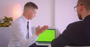 年轻商人陈列膝上型计算机特写镜头画象以成为伙伴的绿色色度屏幕在办公室户内 股票视频