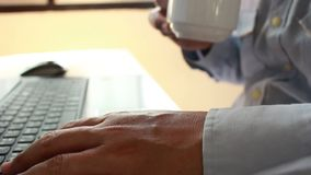年轻商人饮用的咖啡和使用膝上型计算机企业工作的在被弄脏的焦点 股票录像