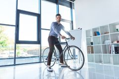 年轻商人骑马自行车和看照相机 库存照片