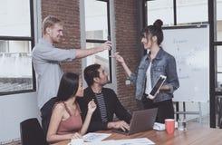 年轻商务伙伴使用小配件,谈话和微笑 免版税图库摄影