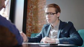 年轻商务伙伴在新的图纸工作,坐在与文件的桌上在咖啡馆内部,谈话 股票视频