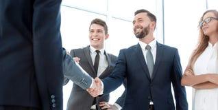 年轻商务伙伴握手在办公室 免版税库存照片