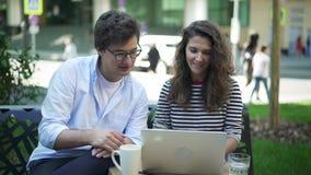 年轻商务伙伴谈论他们的项目在夏天咖啡馆 股票录像