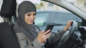 年轻回教夫人在汽车,移动应用程序坐电话,搜寻最佳的路线 股票录像