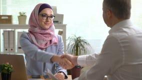 年轻回教女商人与一个白种人人握手在一次会议期间在办公室 影视素材