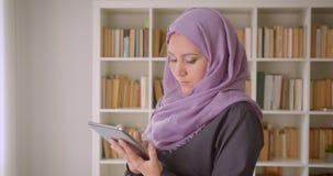 年轻回教女性使用片剂和看照相机身分特写镜头画象hijab的在图书馆里户内 影视素材